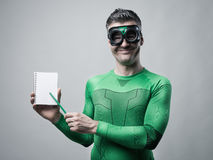 Cheerful superhero with notebook Royalty Free Stock Photography