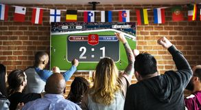 Cheerful supporters watching football at the pub royalty free stock photography