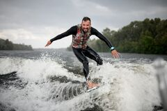 Free Cheerful Surfer Riding Foaming River Wave From Motorboat Royalty Free Stock Photo - 195274825