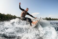 Free Cheerful Surfer Riding Foaming River Wave From Motorboat At Sunny Day. Stock Photo - 195278380