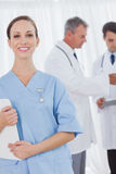Cheerful surgeon posing while doctors talking on background Stock Photo