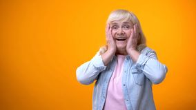 Cheerful surprised elderly lady satisfied with news, discounts and holiday sale stock images