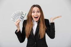 Cheerful surprised lady looking camera while holding dollars in hand. Cheerful surprised businesslady looking camera while holding dollars in hand isolated over royalty free stock image