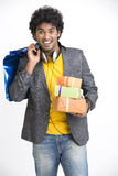 Cheerful surprised overloaded Indian young man surprise with shopping bags and gift boxes Stock Images
