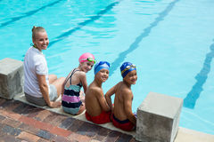 Cheerful swimming instructor and students at pool side Royalty Free Stock Image