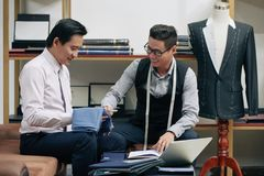 Discussing fabric for suit. Cheerful tailor and client discussing fabric for suit Royalty Free Stock Image