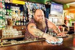 Cheerful tapster cleaning work surface in boozer Stock Photos