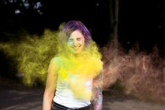 Cheerful tattooed woman with dry color powder Holi exploding aro. Cheerful tattooed young women with dry color powder Holi exploding around her Stock Photos