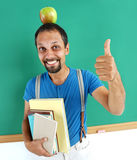 Cheerful teacher with an apple on her head, showing thumbs up. royalty free stock photos