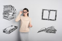 Smiling young teacher standing and touching her glasses. Cheerful teacher. Clever cheerful teacher touching her glasses while waiting for her pupils in the Royalty Free Stock Image