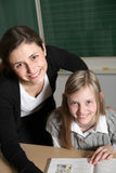 Cheerful teacher and student in the classroom. With textbooks. Both smiling towards the camera. In the background a blackboard can be seen Royalty Free Stock Photo