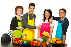 Cheerful team of chefs pointing. Cheerful team of four chefs standing in a line near table with vegetables and one of men pointing to table royalty free stock photography