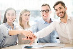 Cheerful team sitting at the table. We work in concert. Pleasant content team sitting at the table and expressing gladness while holding their hands together royalty free stock image