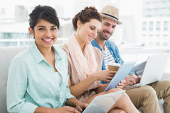 Cheerful teamwork on couch using laptop and tablet Royalty Free Stock Photos