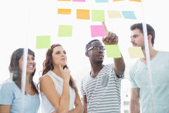 Cheerful teamwork pointing sticky notes and interacting Stock Images