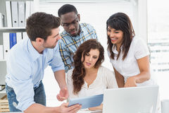 Cheerful teamwork using digital tablet together Royalty Free Stock Photography