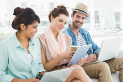 Cheerful teamwork using laptop and tablet on couch Stock Photography