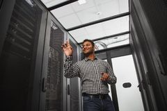 Cheerful IT technician estimating server closet. Electronic devices. Low angle of merry IT technician staying in server room and pointing with finger royalty free stock photography