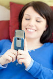 Cheerful teen girl sending a text lying on a sofa Royalty Free Stock Images