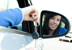 Cheerful teen girl sitting in her car holding keys. After bying a new car Stock Images