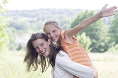 Cheerful teen girls enjoying piggyback ride. Happe friends girls playing outside royalty free stock images