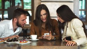 Cheerful teen hipster guy looking at camera while showing her girlfriend video on smartphone, romantic couple in love. Spending time together on cafe terrace stock video footage