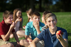 Cheerful Teen Holding Apple. Smiling male teenager with friends holding apple Royalty Free Stock Photo