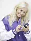 Cheerful teen texting on smartphone. Beautiful smiling teen texting on phone leaning relaxed on the wall royalty free stock images