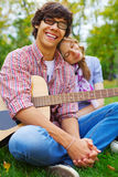 Cheerful teenage couple with guitar in park Royalty Free Stock Image