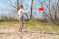 Cheerful teenage girl, blonde is throwing flying disk and smilin Royalty Free Stock Images