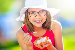 Cheerful teenage girl with dental braces glasses and ice cream. Portrait of a smiling pretty young girl in summer outfit with ice. Cream and teeth braces Stock Photography