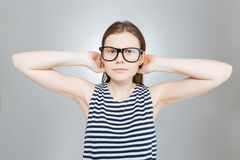 Cheerful teenage girl in glasses standing with hands behind head Royalty Free Stock Image