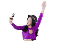 Cheerful teenage girl holds cellphone. Portrait of trendy teenage girl holding cellphone and celebrate her victory in the studio, isolated on white Stock Photos