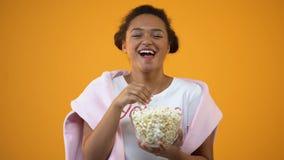 Cheerful teenage girl laughing, enjoying comedy series on tv eating popcorn stock footage