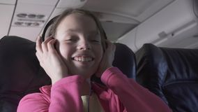 Cheerful teenage girl listens to music on headphones in the cabin of plane while traveling stock footage video. Cheerful teenage girl listens to music on stock video