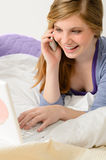 Cheerful teenage girl with phone and laptop Royalty Free Stock Photography