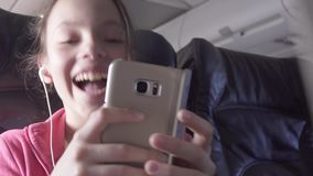 Cheerful teenage girl plays a game on smartphone in the cabin of the plane while traveling stock footage video. Cheerful teenage girl plays a game on a stock footage