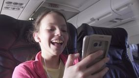 Cheerful teenage girl plays a game on smartphone in the cabin of the plane while traveling stock footage video. Cheerful teenage girl plays a game on a stock video footage
