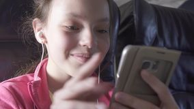 Cheerful teenage girl plays a game on smartphone in the cabin of the plane while traveling stock footage video. Cheerful teenage girl plays a game on a stock video