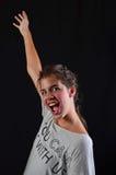 Cheerful teenage girl. Shouting loudly to express joy, studio shot against black background Stock Photography