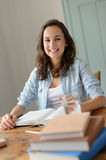 Cheerful teenage girl studying at home Stock Photo