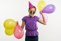 Cheerful teenage girl 12,13 years old, with balloons, in festive hat on white background. stock photo