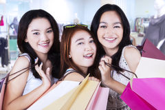 Cheerful teenage girls at mall. Group of happy teenage girls with shopping bags smiling at the camera in the mall Stock Photo