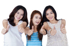Cheerful teenage girls showing thumbs up Stock Photo