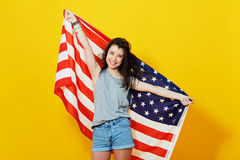 Cheerful teenage patriotic girl with US flag. Cheerful teenage patriotic girl holding american flag of the U. S. on yellow background in studio Royalty Free Stock Photos