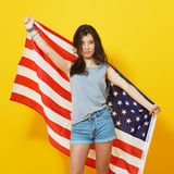 Cheerful teenage patriotic girl with US flag. Cheerful teenage patriotic girl holding american flag of the U. S. on yellow background in studio Royalty Free Stock Photo