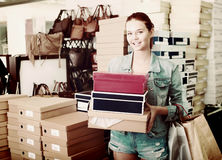 Cheerful teenager girl holding boxes in shoes boutique Stock Photos