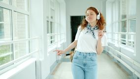 Cheerful teenager in headphones enjoying music dancing in school hall having fun. Wearing casual clothing and holding backpack. People and lifestyle concept stock video footage