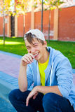 Cheerful Teenager outdoor. Cheerful Teenager sit on the City Street royalty free stock photos
