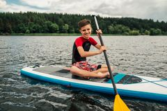 Cheerful teenager sitting on a sap surf and rowing with an oar stock photos